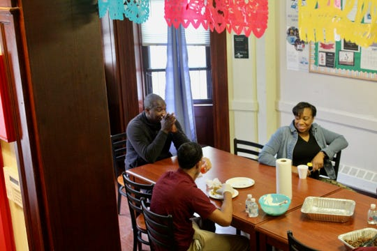 Youths eat lunch with staff members at a big family-style kitchen table at a limited-secure Close to Home facility in Brooklyn, New York.