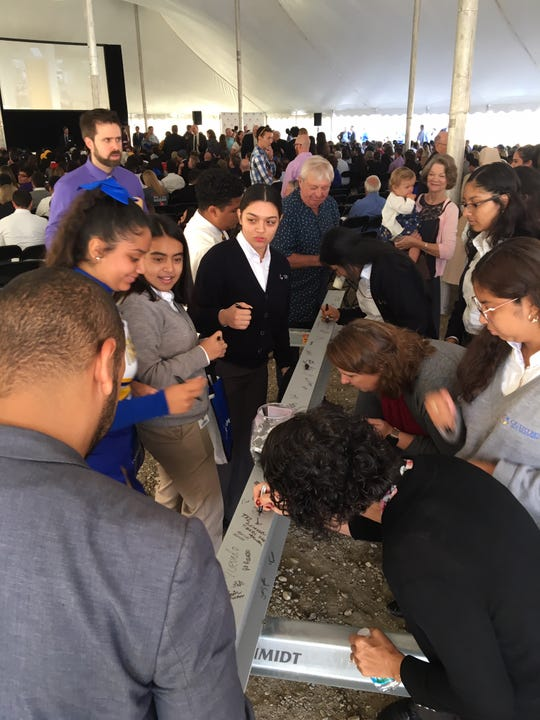 Students, staff and supporters line up to sign one of the beams that will be installed in the new $33 million, 100,000-square-foot Cristo Rey Jesuit High School, during the groundbreaking ceremony Wednesday, Sept. 18, 2019.