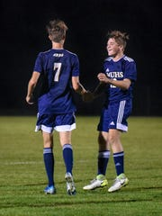 Charles Holton congratulates Marquette teammate Luke Thew (7) on one of his goals against Brookfield Central in a boys soccer match Tuesday, September 17, 2018, at Quad Park in Milwaukee, Wisconsin.