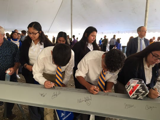 Students line up to sign a beam that will be installed in the new Cristo Rey Jesuit High School during the groundbreaking ceremony Wednesday, Sept. 18, 2019. The new $33 million school will be built at 1818 W. National Ave. in Milwaukee.
