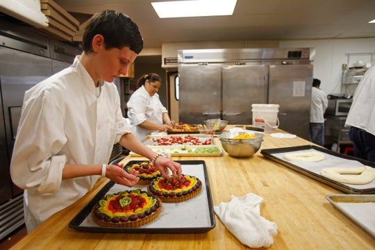 Megan Mahalick, front, makes fruit tarts with Lupe Madrigal at Regina's Bay Bakery in 2009.