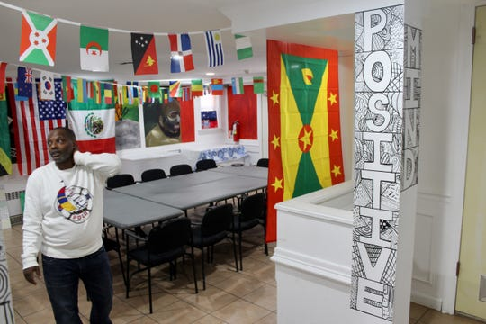 Edwidge Michel shows the different flags on display in the Close to Home facility in Queens, New York, as part of a cultural celebration the youths held for a family engagement event.