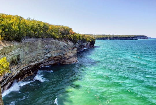 The blue-green waters of Lake Superior churn below the sandstone cliffs in Pictured Rocks National Lakeshore on Sept. 14, 2019.