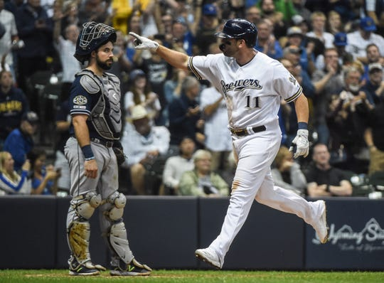 Mike Moustakas celebrates as he heads to the dugout after blasting a solo home run leading off the eight inning that gave the Brewers the lead for good over the Padres.