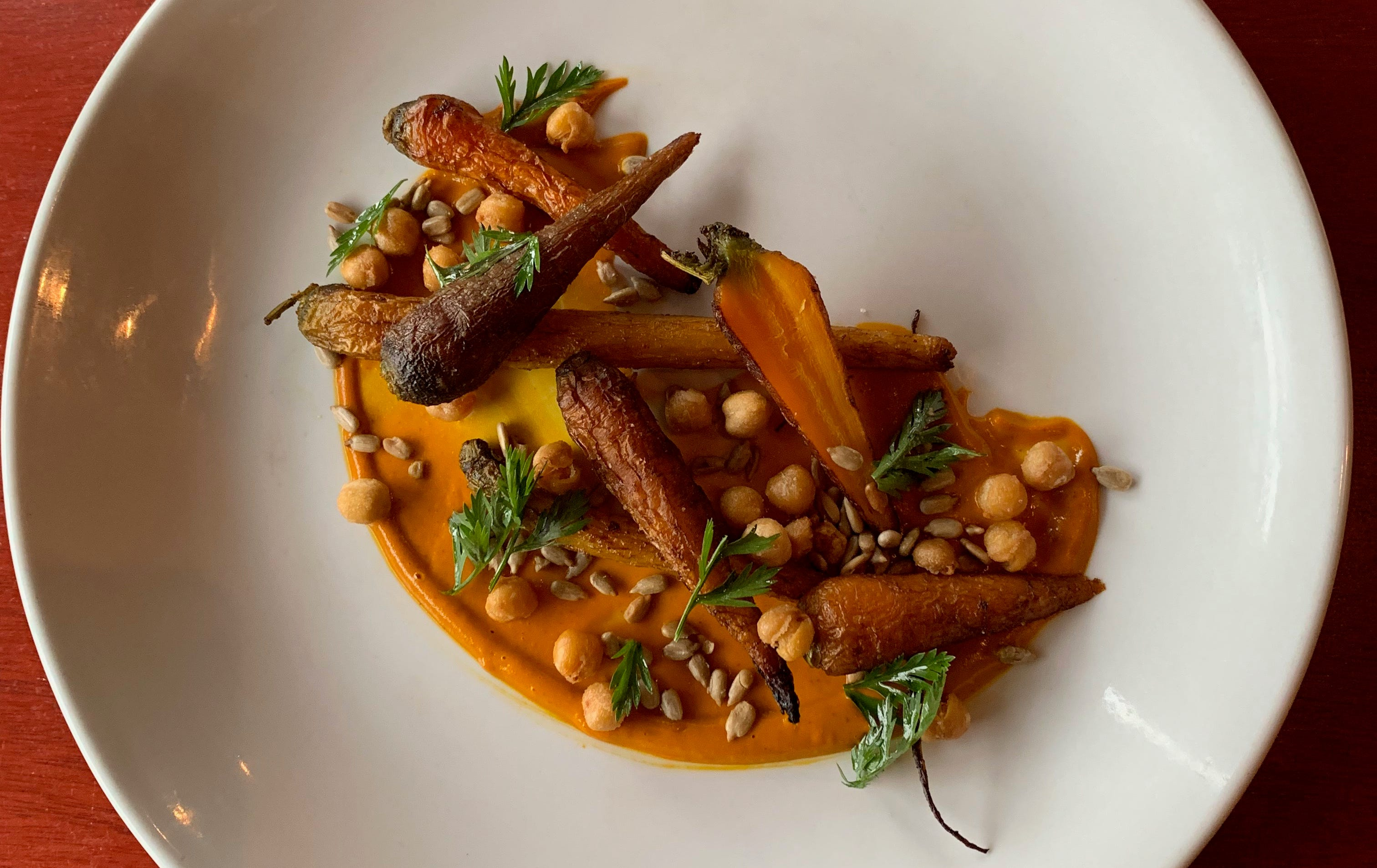 Carrot barbecue sauce is the bed for roast carrots, fried chickpeas and sunflower seeds, a dish at the Diplomat, 815 E. Brady St.