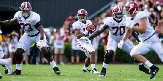 Alabama quarterback Tua Tagovailoa (13) looks to pass from behind Alabama offensive linemen Evan Neal (73) and Alex Leatherwood (70) against South Carolina at Williams-Brice Stadium in Columbia, S.C., on Saturday September 14, 2019.
