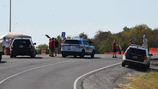 Maury County Sheriff's personnel keep traffic moving as striking workers gather outside the north gate of the General Motors plant Wednesday, Sept. 18, 2019, in Spring Hill, Tenn.