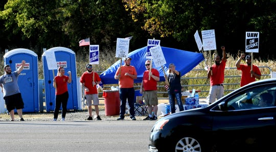 Striking UAW workers wave to cars on Main Street about a mile from the General Motors plant Wednesday, Sept. 18, 2019, in Spring Hill, Tenn.