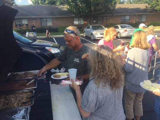 Joel Lively (left) of Papa Joe's Hometown BBQ serves up meals in the parking lot of Pataskala Oaks Sept. 17.