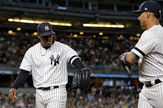 Sep 17, 2019; Bronx, NY, USA; New York Yankees pitcher Luis Severino (40) slaps gloves with New York Yankees second baseman Gleyber Torres (25) on the way into the dugout against the Los Angeles Angels during the fourth inning at Yankee Stadium. Mandatory Credit: Adam Hunger-USA TODAY Sports