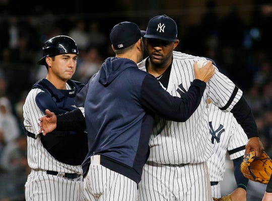 Sep 18, 2019; Bronx, NY, USA; New York Yankees starting pitcher CC Sabathia (52) and manager Aaron Boone (17) hug after Sabathis was taken out of the game against the Los Angeles Angels during the third inning at Yankee Stadium. Mandatory Credit: Andy Marlin-USA TODAY Sports