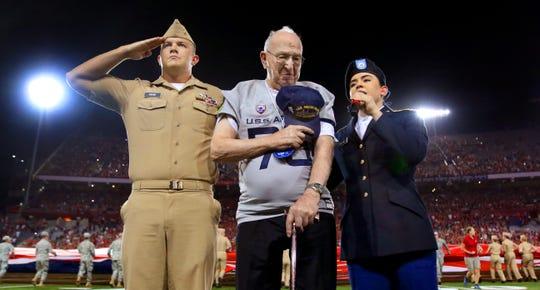 Pearl Harbor and USS Arizona veteran Lauren Bruner, center, stands for the singing of the national anthem before the Arizona Wildcats take on Hawaii at Arizona Stadium, Saturday, Sept. 17, 2016, Tucson, Ariz.