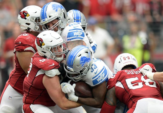Lions running back Kerryon Johnson (33) is wrapped up by Cardinals defensive end Zach Allen (97) during a game Sept. 8 at State Farm Stadium.
