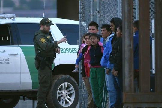 Un agente de la Patrulla Fronteriza habla con migrantes.