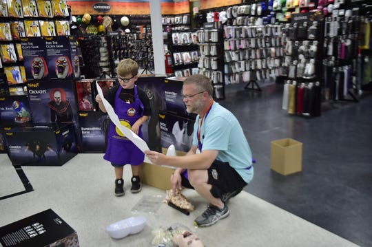 """Declan McMullen, 6, loves everything that has to do with Halloween. His favorite store, Spirit Halloween, invited him in as an honorary employee to build some of the spookiest decorations - animatronics.  He decided to build """"Bloodthirsty Betty,"""" with the help of Matt Thomas, district sales manager. Thomas told Declan the most important step is reading the directions."""