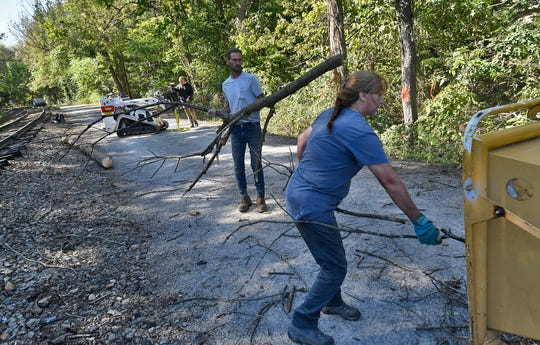 Shawn Mehaffie and sister Sherry Shipley of Yard Images load tree debris into a chipper while removing dead trees  from the Heritage Rail Trail between miles 18-19 to make the area safer for trail users. The trail will be closed through Friday. Wednesday, September 18, 2019.