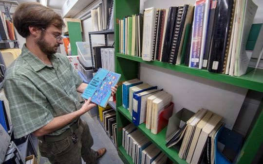 Library director John Grayshaw pulls a book from a basement reference area of the Middletown Library dedicated to the Three Mile Island generating station.