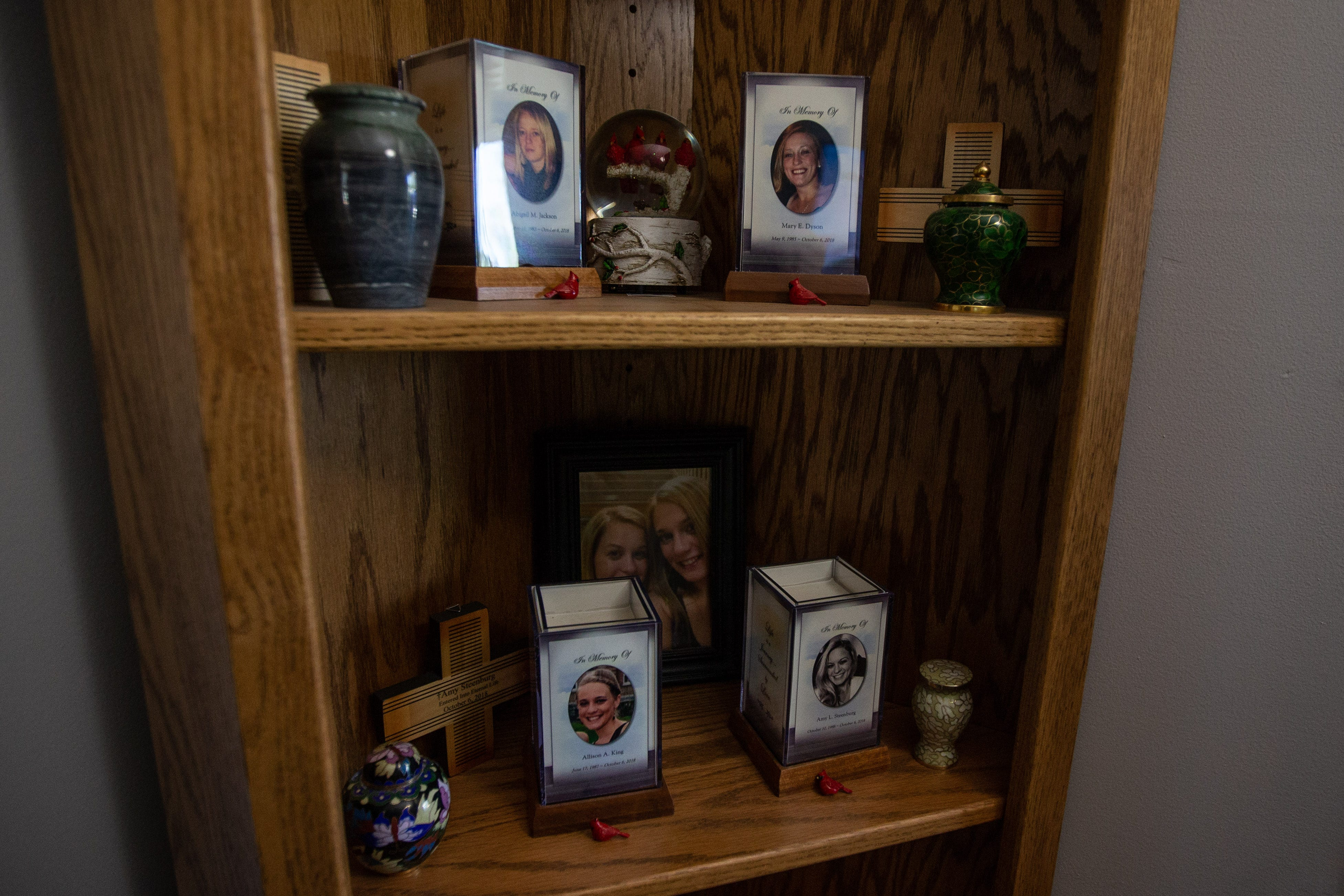 Four small urns are placed near photos of each one of Tom and Linda King's four daughters who died on Oct. 6, 2018 in the limousine crash in Schoharie, New York. The curio cabinet is nestled in the livingroom of the Kings' home in Amsterdam, New York, and is a small, modest memorial honoring their daughters: Abigail Jackson, Mary Dyson, Allison King and Amy Steenburg.