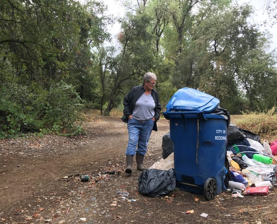Dot Van Cleave, a Shasta Support Service volunteer, checks out trash strewn around a city of Redding garbage can on the side of a trail in the Henderson Open Space area in Redding.