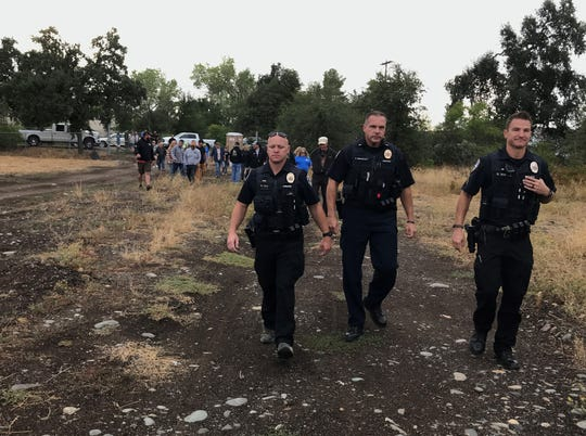 Redding police school resource officer Eddy Gilmette, left, Lt. Pete Brindley, center, and Sgt. Danny Smetak lead a group of about 30 people on a tour of the Henderson Open Space on Wednesday, Sept. 18, 2019.