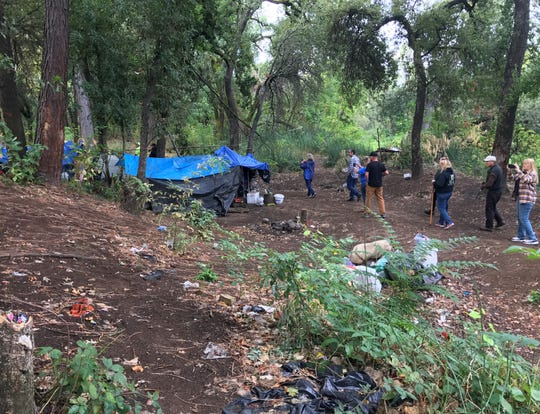 Community members walk by one of the many encampments in the Henderson Open Space in Redding on Wednesday, Sept. 18, 2019.