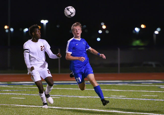 Washington High School player Jeremie Benson watches as O'Gorman High School player Riley Aarbo heads the ball in a soccer match Tuesday, September 17, at O'Gorman.