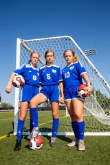 Sisters Ellie, Sidney and Ava Schock pose for a portrait at Sioux Falls Christian on Tuesday, Sept. 10, 2019. All three girls play for the Sioux Falls Christian Chargers.
