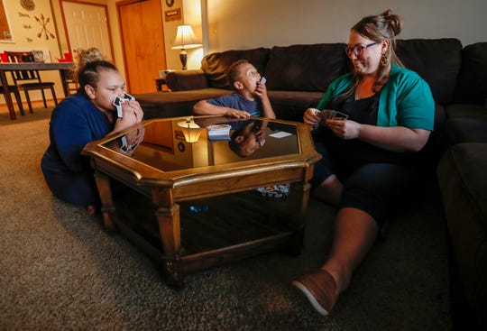 Kristina Hazeltine plays a game of Uno Dare with her children A.J. Wilson, 12, left, and Deacon Hazeltine, 6, center, at their home on Monday, Sep. 16, 2019, in Springfield, Mo.