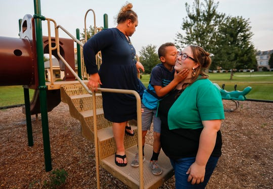Deacon Hazeltine, 6, gives his mom Kristina Hazeltine a kiss on the cheek after playing with his sister A.J. Wilson, 12, on the playground outside their home on Monday, Sep. 16, 2019, in Springfield, Mo.