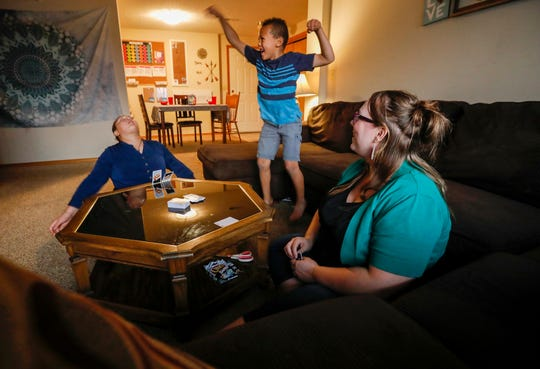Deacon Hazeltine, 6, center, celebrates after winning a game of Uno Dare against his mother Kristina Hazeltine and sister A.J. Wilson, 12, at their home on Monday, Sep. 16, 2019, in Springfield, Mo.