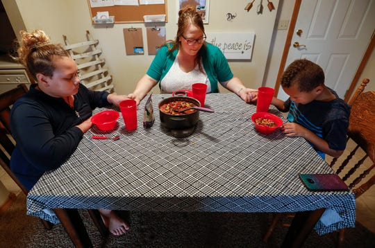Kristina Hazeltine prays with her children A.J. Wilson, 12, left, and Deacon Hazeltine, 6, right, before eating dinner together on Monday, Sep. 16, 2019, in Springfield, Mo.