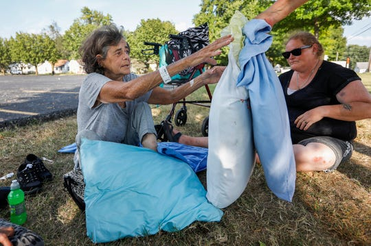 Janetta Stevens is handed her sheet and pillows with Patty Belt on Tuesday, Sept. 18, 2019, in Springfield, Mo. Stevens sleeps outside now because the shelter only allows women to stay there for three months, and her time was up.