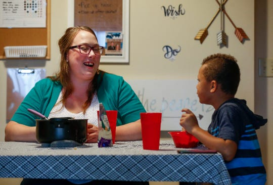 Kristina Hazeltine laughs at something her son Deacon Hazeltine, 6, said as they eat dinner together on Monday, Sep. 16, 2019, in Springfield, Mo.