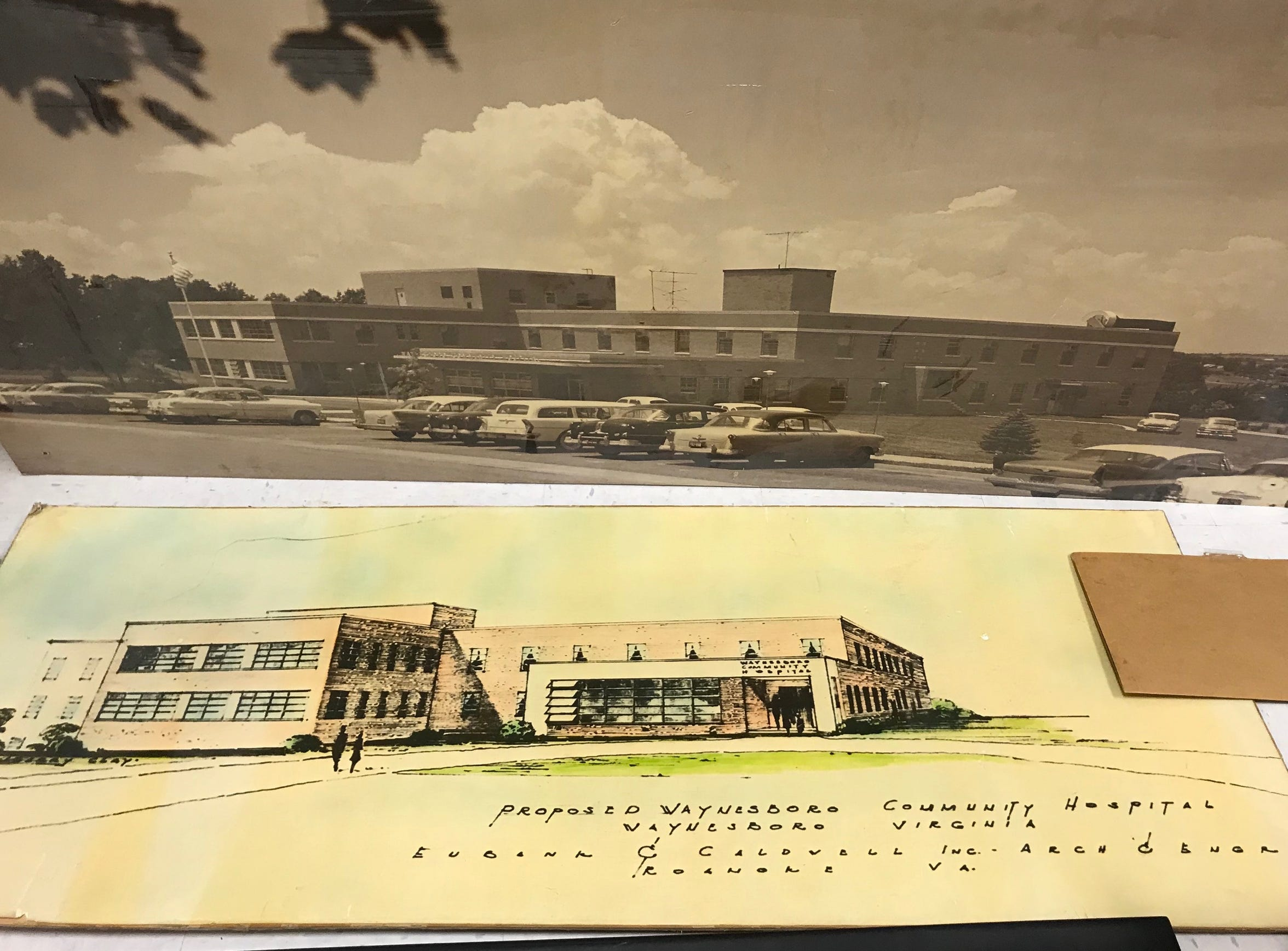 Architectural drawings of Waynesboro Community Hospital sit on the floor beside a photograph of the hospital in a storage room at Augusta Medical Center in Fishersville, Va. (Drawings rendered by Eubank and Caldwell.)