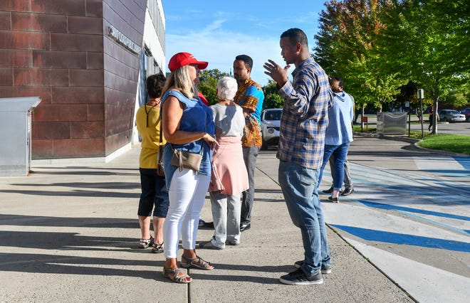 People talk outside the St. Cloud Public Library after a planned forum on hate crimes was postponed Wednesday, Sept. 18, 2019, in St. Cloud.
