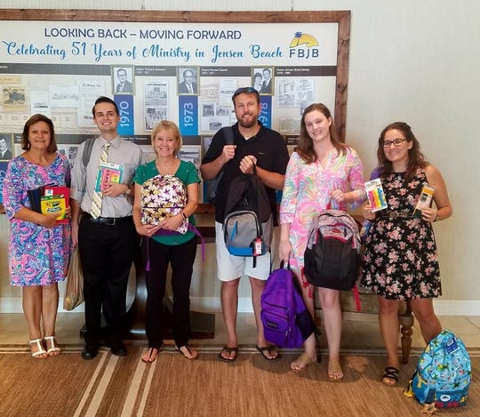 First Baptist Church of Jensen Beach members George Ann Braden, left, Youth Pastor Robbie Gray, Kay Maine, Chris Urban, Ashley Braden-Knowles and Amy Stevenson hold some of the backpacks and school supplies donated to the Hibiscus Children's Shelter in Jensen Beach.