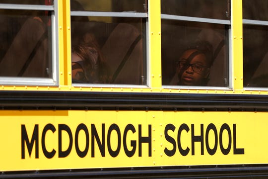 A child is visible through a window as a school bus leaves the McDonogh School campus after a reported explosion, Wednesday, Sept. 18, 2019, in Owings Mills, Md. An explosion in the boiler room at the at the school injured a child and two adults, according to reports. (AP Photo/Julio Cortez)