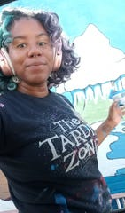 Brea'n Thompson, the local artist who created the new mural at The Deli Planet & Drinkery outside Sheppard Air Force Base.