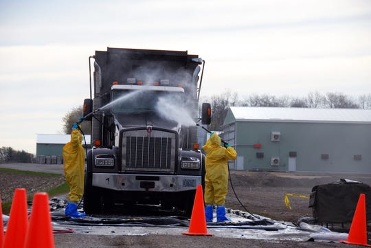 Sgt. Parminder Singh and Spc. Lacy Taylor, both Soldiers with the Hartford, Wis.-based 457th Chemical Company, decontaminate a vehicle leaving a poultry farm in Lake Mills, Wis., April 29, 2015. The Wisconsin National Guard that was called to state active duty to assist the Wisconsin Department of Agriculture, Trade and Consumer Protection in its response to Avian Flu outbreaks at several sites across the state.