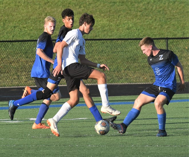 Coshocton's Nico Barbarossa takes on Zanesville's Gabe Dolen (8) in Tuesday's match. The teams played to a 3-3 tie.