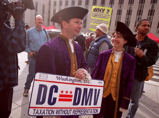 "Mark Phillips and Karen Beriss show off an enlarged version of the new ""Taxation Without Representation"" license plate in Washington, D.C., on Nov. 4, 2000."