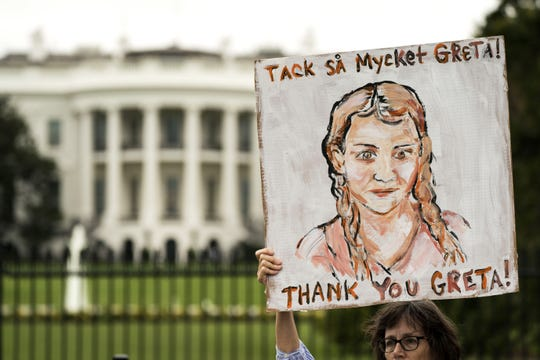 A woman holds a sign with the image of  teenage Swedish climate activist Greta Thunberg during a strike to demand action be taken on climate change outside the White House on September 13, 2019 in Washington, DC.