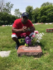 Demetrius Johnson poses with the grave of his mother, Glenda Johnson, who passed away while Johnson was in prison.