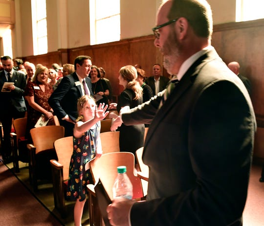 Julia Levesque slaps-five with her father. George. as he exits the stage after delivering the convocation address at McMurry University on Thursday.