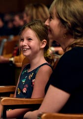 Julia Levesque, 9, laughs at her father George's remarks about telling her the same fact time and again during his convocation address Thursday at McMurry University.