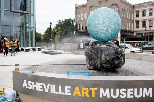 "Artist Henry Richardson uses a hose to wash the boulder underneath his glass orb outside of the Asheville Art Museum as his piece"" Reflections on Unity"" is installed on Sept. 19, 2019."
