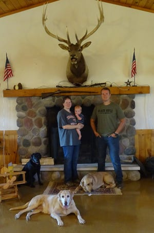 Ruth Malpas, holding her son Benjamin, and her brother Samuel Ballou stand in front of a fireplace at Elkhorn Lake Hunt Club, which they operate along with their parents. The club's annual family field day will be Sept. 28.