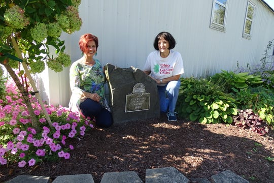 Shirley Chapman and Mary Lee Minor of the Earth, Wind and Flowers Garden Club kneel next to a plaque commemorating an award issued by the Ohio Association of Garden Clubs in 1999.
