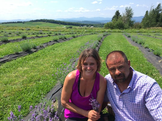 Michele Judd and Pierre Capron sit in a field at Lavender Essentials of Vermont in Derby Line on July 26, 2019.