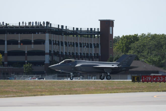 Onlookers watch one of Vermont's first two F-35 fighter jets from the Burlington International Airport parking garage in South Burlington on Thursday, Sept. 19.